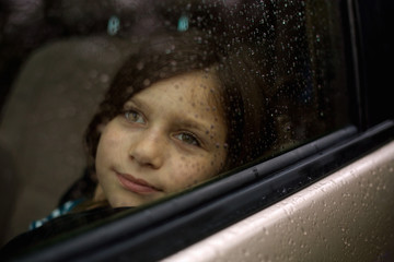 Portrait of a girl looking through a rainy window.