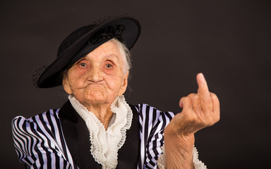 Old woman showing her middle finger