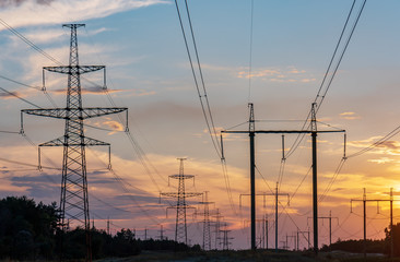 high-voltage lines against the background of electrical distribution stations at sunrise.