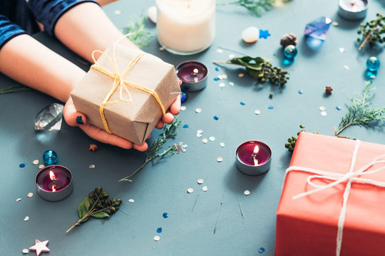 christmas presents giving tradition. hands holding craft gift package against blue decorated background. holiday spirit and seasonal embellishments concept.