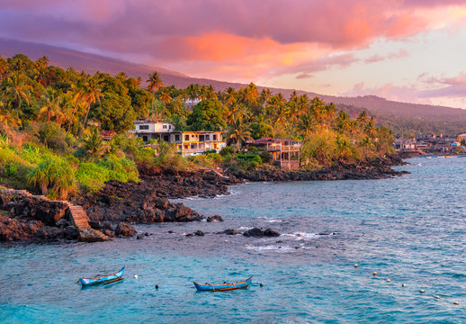 Sunset boats in holiday paradise resort on Grand Comore island, Comoros. Beautiful sunset light of sun in the sea. Villas on the beach with private beach. Moroni Comoros, Itsandra beach resort hotel