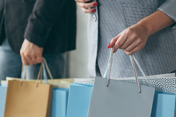 shopping and season sale. cropped shot of man and woman with multiple bags in hands.