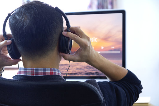 Back side of an Asian man wearing black heaphones in front of desktop computer screen listen to a music streaming with entertainment music application screen. Copy space included.