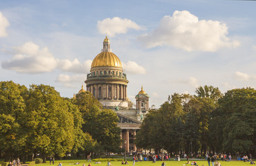 Park with a lawn, where a lot of people resting in front of St. Isaac's Cathedral.Saint-Petersburg.Sunny autumn day.