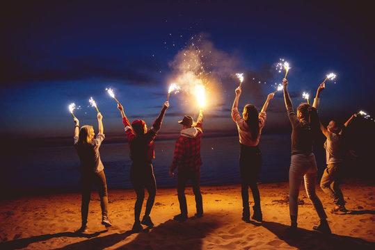 Group friends dusk signal fire beach