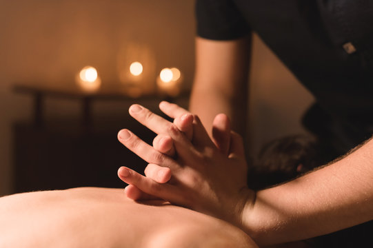 Men's hands make a therapeutic neck massage for a girl lying on a massage couch in a massage spa with dark lighting. Close-up. Dark Key