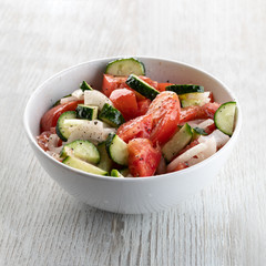 Sliced Cucumber, Tomato, Onion Salad With Olive Oil In A Plate On A White Wooden Background. Close Up.