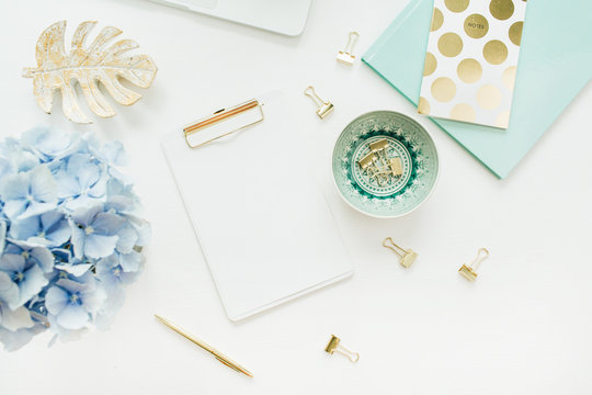 Modern home office desk workspace with blank paper clipboard, hydrangea flower bouquet on white background. Flat lay, top view mock up.