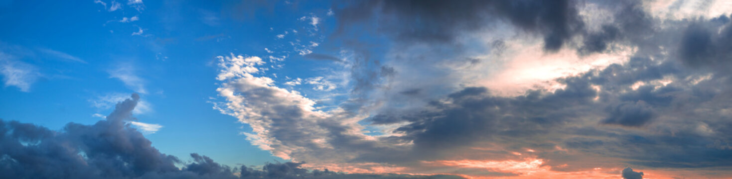 Beautiful panorama of the evening blue sky with colored clouds