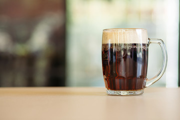 Horizontal photo of glass cup full of beer standing on smooth wooden surface. Cold dark summer drink for day heat. Fresh with thick high foam. Light blurred background. Concept of drinks shooting.
