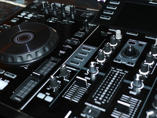 DJ professional music console. Wide angle photo of black sound mixer controller with knobs and sliders. Professional audio mixing console with faders and adjusting knob
