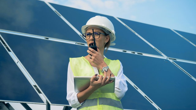 An engineer works with devices, standing on a roof near solar batteries. Alternative, green energy concept.