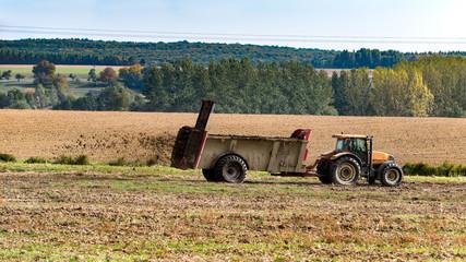 tracteur agricole qui fait un épandage de fumier sur le champ Fototapete