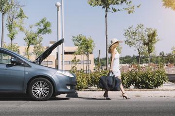 Girl leaving broken car with baggage