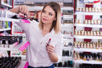 Girl looking for lipstick tube in cosmetics shop