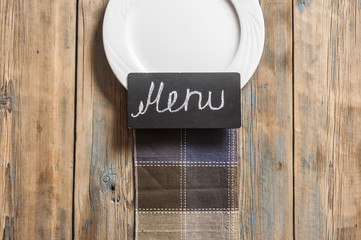 restaurant menu design. Restaurant menu with empty and white plate on wooden background. Top view with copy space for text