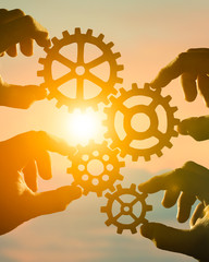 Business concept idea. four hands of businessmen collect a puzzle from gears. Cooperation, teamwork, strategy, creativity, innovation.