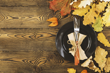 Autumnal table setting for Thanksgiving dinner. Empty plate, cutlery, colored leaves on wooden table. Fall food concept.