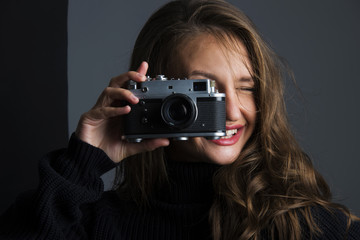 young woman holding old retro analog photo camera smiling banner concept