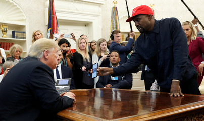Rapper Kanye West shows President Trump image of airplane concept on his mobile phone during meeting in the Oval Office at the White House in Washington