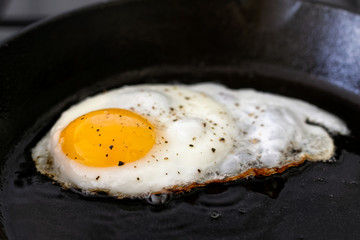 Closeup of fried egg in cast iron frying pan sprinkled with ground black pepper.