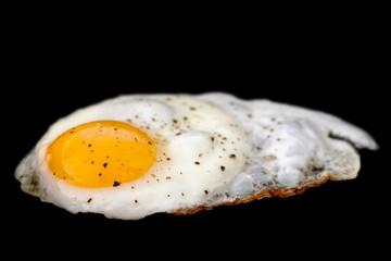 Single fried egg sprinkled with ground black pepper isolated on black.
