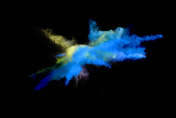 Abstract forms of powder paint and flour combined  together explode in front of a black background to give off abstract  multi colored cloud forms.
