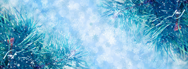 Christmas background with fir branches, glow, snowflakes and bokeh.
