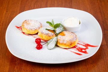 Delicious syrniki with cream