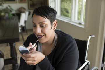 Woman in wheelchair putting on makeup