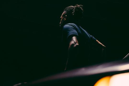 Model in the Dark leaning against car