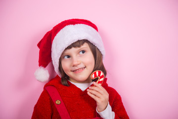 Cute smiling little girl in Santa hat and Christmas costume holding caramel can in studio on pink background.