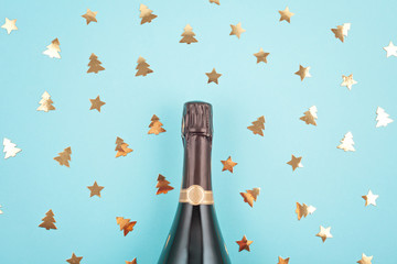 Creative photo of champagne bottle with confetti. Flat lay of christmas, new year celebration