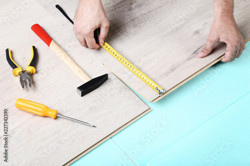 Man Installing Timber Laminate Flooring With Tools Stock Photo And