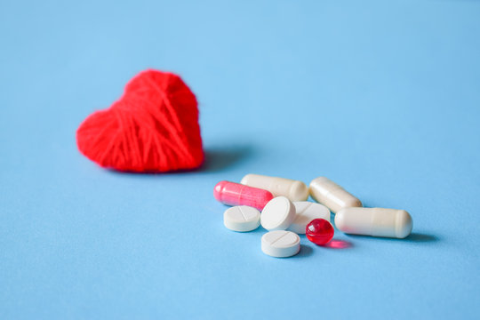 Blood pressure pills. White and red various pills and capsules with red heart on blue background. Concept medical treatment, Medicine for diabetes and High blood pressure.