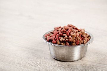 Dry pet food in bowl on timber flooring at home