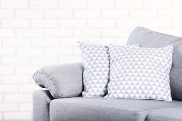 Modern grey sofa with pillows on brick wall background