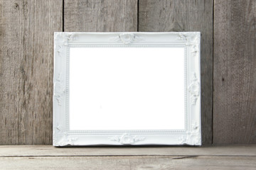 Empty white picture frame on wooden background.