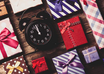 colorful gifts and black clock on the brown wooden table