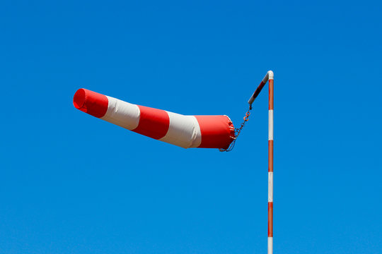 A fully extended with strong wind windsock against the blue sky