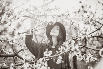 Portrait of a beautifulwoman in blossom apple tree garden in spring time on sunset. Image in black and white color style
