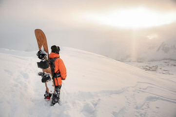 Foto auf AluDibond Wintersport Rear view of professional snowboarder standing on the mountain peak with a board