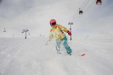 Active woman snowboarder in bright sportswear riding down the mountain slope against the sky and cableway