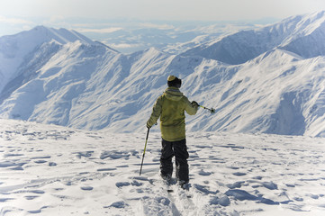 Back view of active skier in bright yellow sportswear riding down the mountains