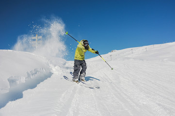 Active skier in bright yellow sportswear riding down the mountains