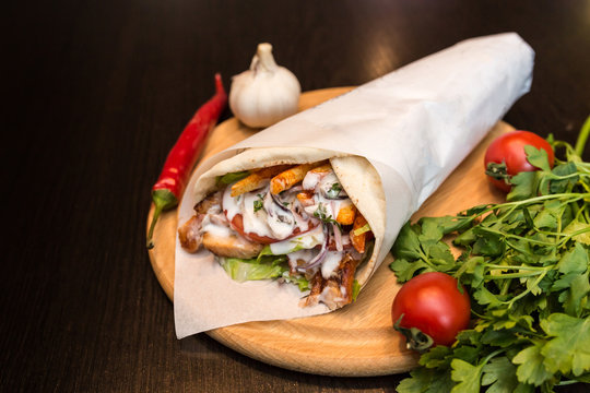 Shawarma sandwich giros - fresh roll of thin lavash (pita bread) filled with grilled meat, mushrooms, cheese, cabbage, carrots, sauce, green. Traditional Eastern snack. On a wooden background