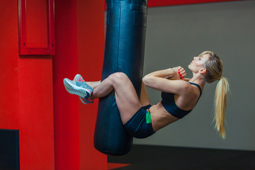 Young beautiful woman doing abs workout functional crossfit training on punching bag. Strong muscular sporty girl ready for active exercise in sport gym. Strength and motivation. Self defense training