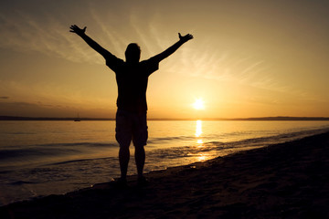 silhouette of man with open arms raised at sunset