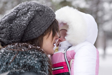 A young mother plays with a baby on the street during a snowfall