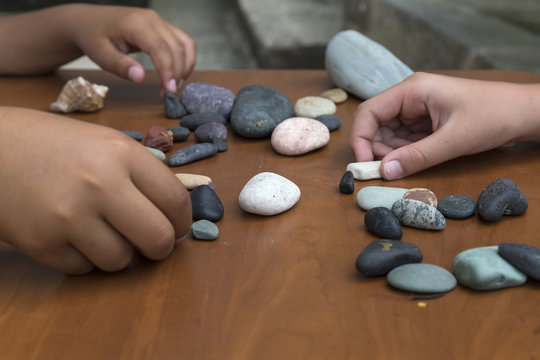 The child is playing with stones from children's activities.kid draws something for her handcraft picture.